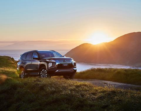 A black Pajero Sport parked on a hill with sun rising from a mountain beside sea