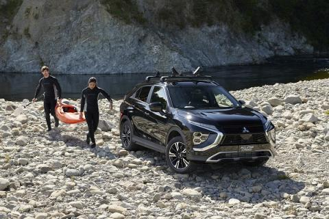 Man and woman carrying a kayak towards an Eclipse Cross parked by a river