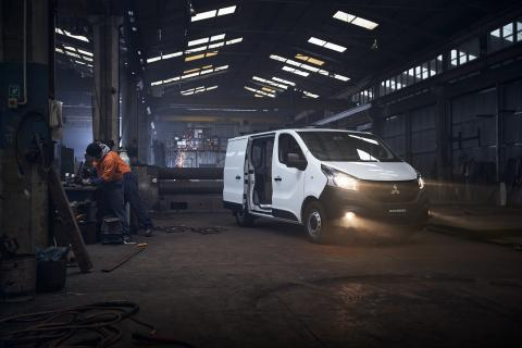 White Mitsubishi Express Van and a mechanic working on side
