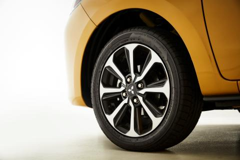 A close up shot of left side front wheel of a yellow Mitsubishi Mirage