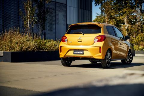 A full shot of the back of a yellow Mitsubishi Mirage from distance