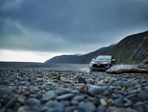 A black Pajero Sport driving over a rocky river bank