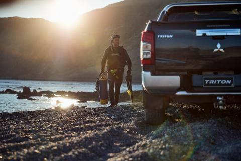 A Scuba diver walking on the rocks with his gear in hand towards his Triton ute