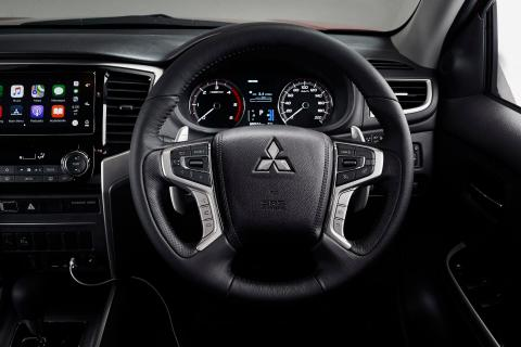 The interior of a Mitsubishi Triton showing the steering wheel and dashboard