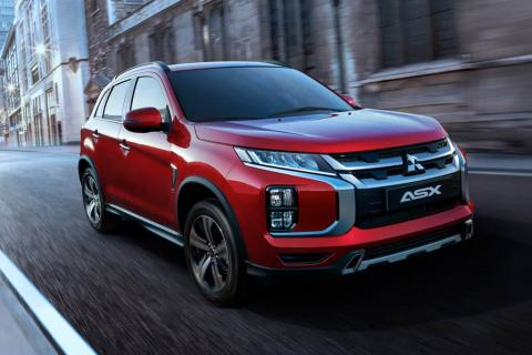 An angle shot from front of a red Mitsubishi ASX running on street