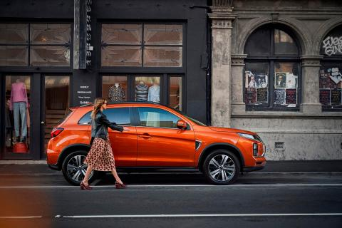 A women walk passing an orange Mitsubishi ASX parking front of a old building