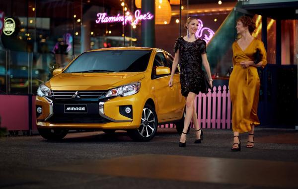 Two nicelydressed females walking past a Mitsubishi Mirage outside a bar at night